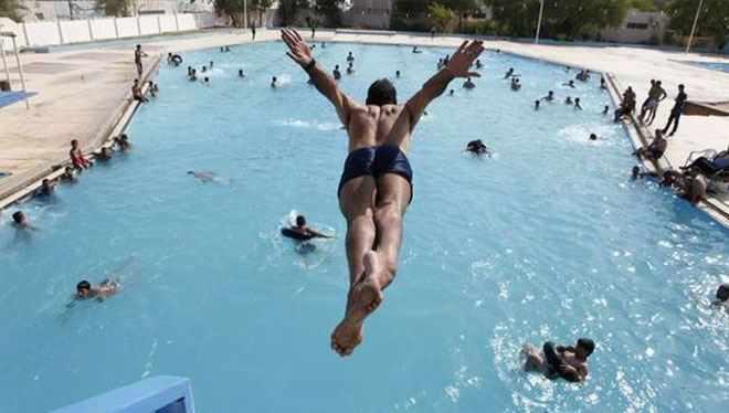 мужчина ныряет в бассейн