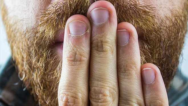 бородатый мужчина прикрывает рот