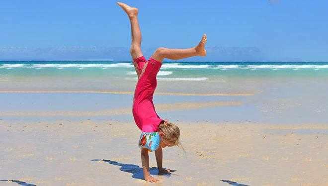 девочка делает колесо на пляже