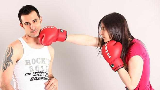 девушка бьет боксерскими перчатками парня