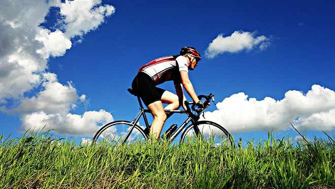 велосипедист на фоне травы